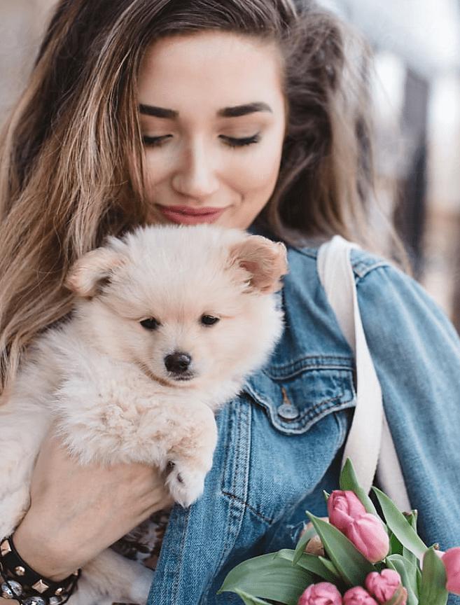 Eine junge Frau in Jeansjacke mit hellbraunen Haaren hält einen Hundewelpen mit hellem Fell auf dem Arm.